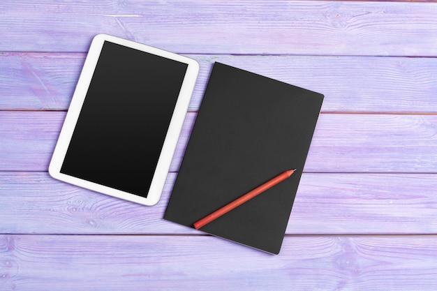 Oficina de tableta digital y bloc de notas en madera púrpura