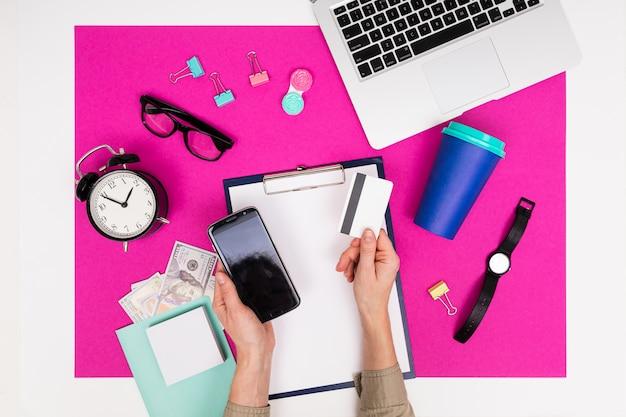 Oficina de trabajo. papelería, micrófono, teléfono, computadora portátil y tarjeta de crédito en una mesa rosa con marco