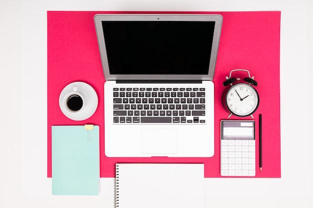 Oficina de trabajo. portátil, taza, reloj, bloc de notas con maqueta sobre fondo rosa con marco