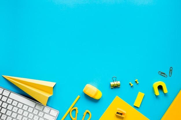 Oficina y útiles escolares sobre fondo azul.