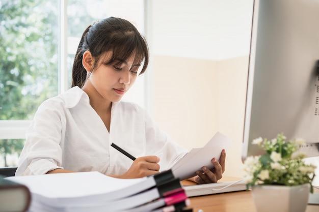 Las oficinas asiáticas de la mujer de negocios comprueban el trabajo para saber si hay la pila de papeles de documentos inacabados en la computadora
