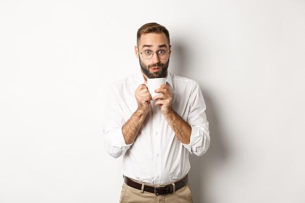Oficinista feliz bebiendo café caliente y mirando emocionado, chismeando, de pie sobre fondo blanco.