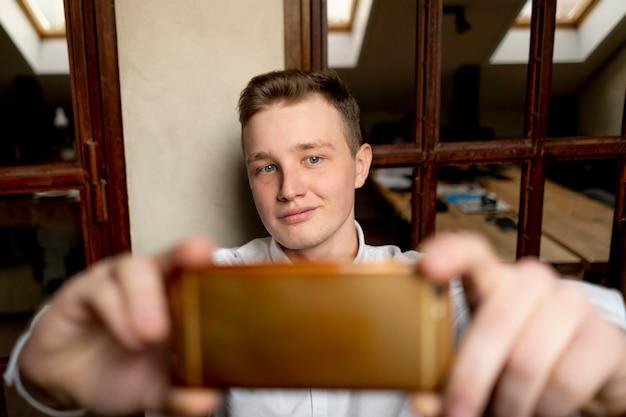 El oficinista feliz joven hace el selfie en el lugar de trabajo con smartphone
