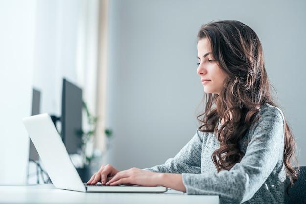 Oficinista joven que usa la computadora portátil. blogger trabajando en laptop.