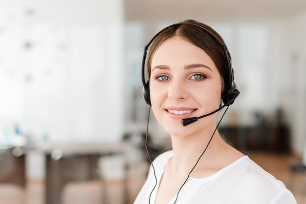 Oficinista joven sonriente con un receptor de cabeza que contesta en un centro de atención telefónica, mujer que habla con los clientes.