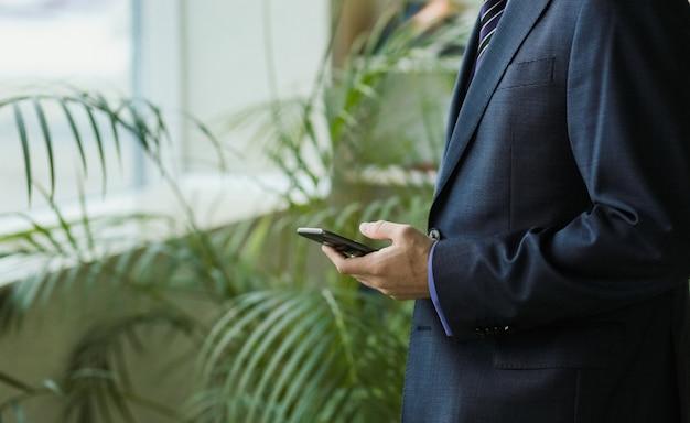Oficinista masculino en traje con teléfono inteligente cerca de ventana y palmeras