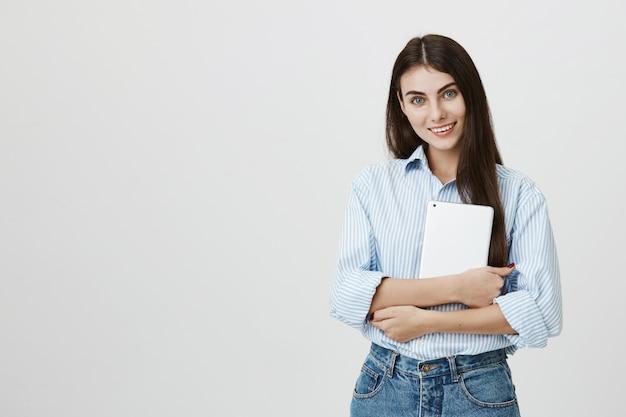 Oficinista mujer atractiva sosteniendo tableta digital y sonriendo