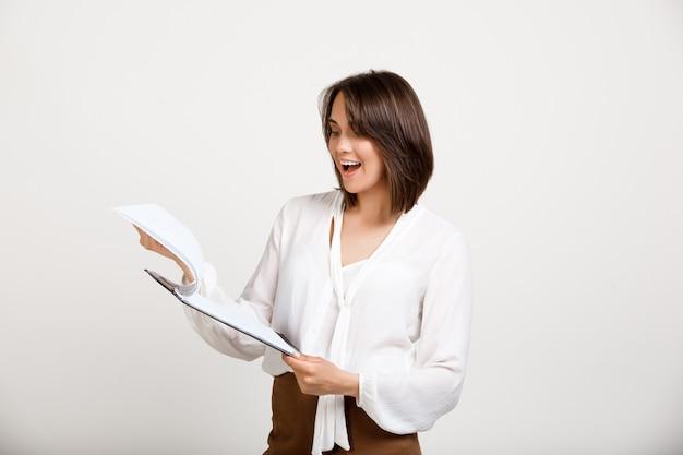 Oficinista mujer leyendo documentos