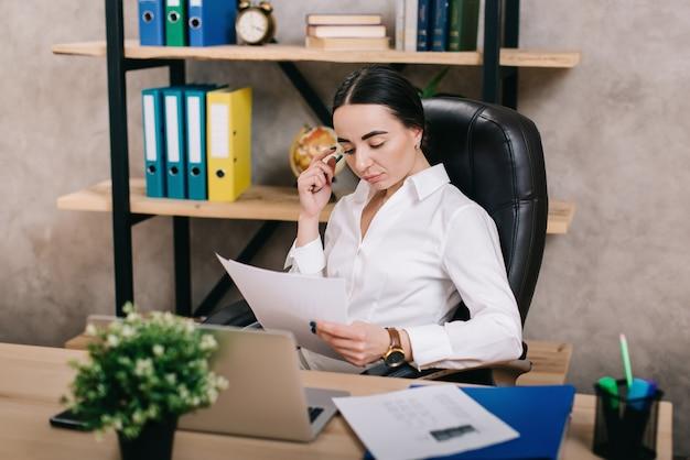 Oficinista mujer viendo documentos en el lugar de trabajo