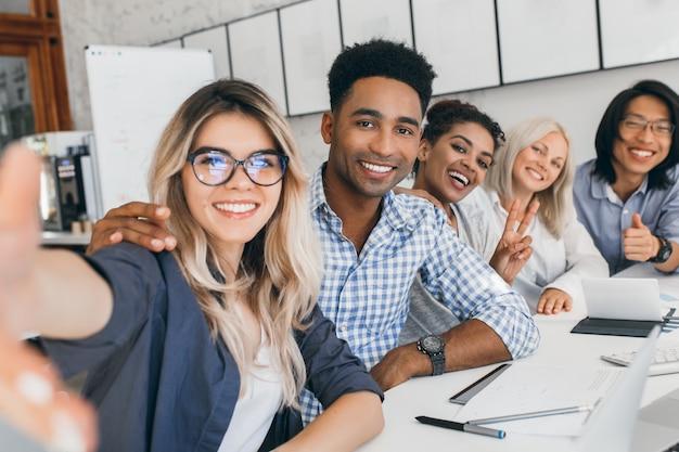 Oficinista negro en camisa a cuadros abrazando secretaria rubia mientras ella hace selfie. jóvenes directivos de empresa internacional divirtiéndose durante la reunión.