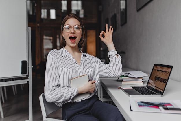 Oficinista de niña alegre muestra signo ok. retrato de mujer en pantalones y blusa ligera en el lugar de trabajo.