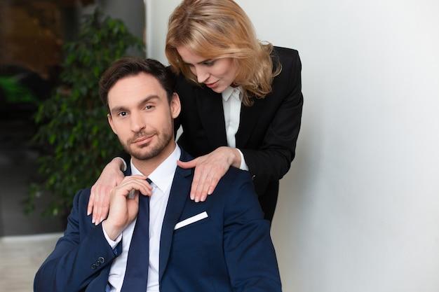 Oficinista seduce al jefe masculino. mujer joven acariciando los hombros masculinos. empoderamiento de las mujeres
