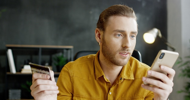 Oficinista de sexo masculino joven sentado en la mesa, con tarjeta de crédito y compras en línea en la computadora portátil.
