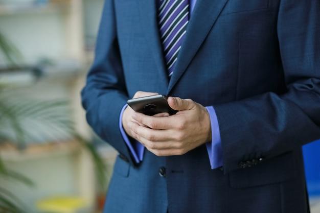 Oficinista en traje con teléfono inteligente cerca de ventana y palmeras