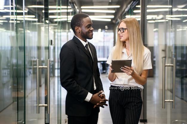 Oficinistas africanos masculinos y caucásicos femeninos con tablet pc de pie en el pasillo de la oficina vacía y discutiendo el nuevo proyecto.