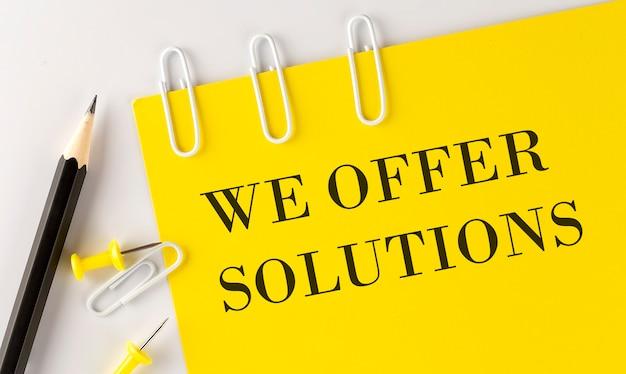 Ofrecemos soluiones palabra en papel amarillo con herramientas de oficina en la superficie blanca