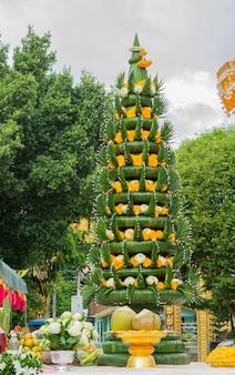 Ofrenda de arroz. de arroz cocido bajo un arreglo cónico de hojas dobladas de plátano y flores en el templo.