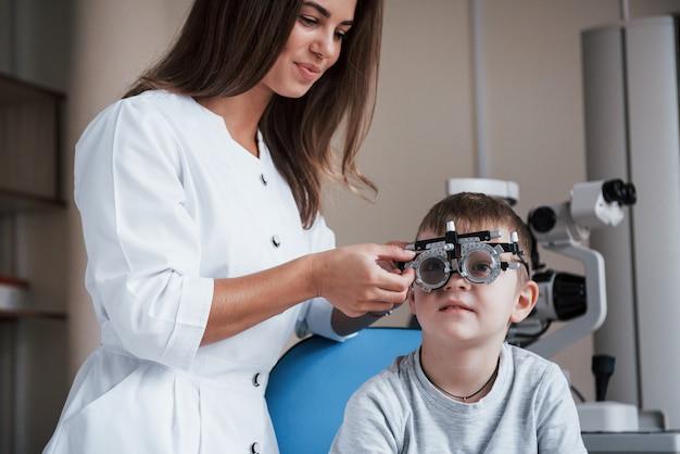Oftalmolog corrige el dispositivo. niño sentado en el gabinete del médico y haber probado su agudeza visual.