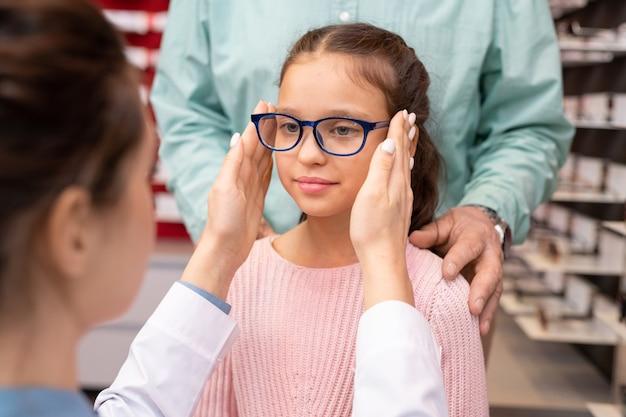 Oftalmóloga joven en bata blanca poniendo un par de anteojos nuevos en la cara de la niña linda que visita el consultorio médico con su abuelo
