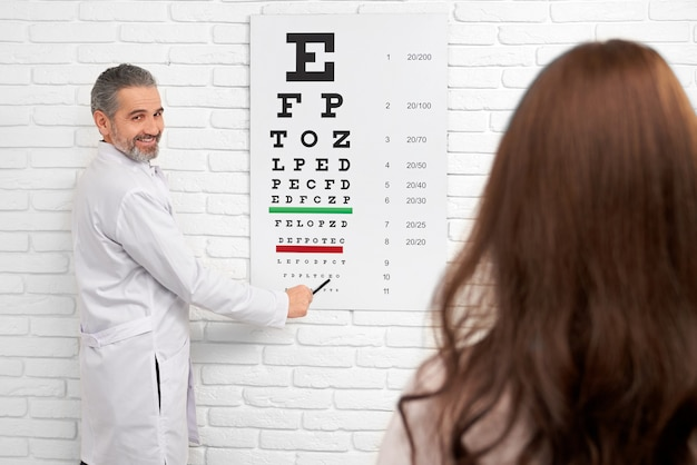 Oftalmólogo apuntando a la carta de ojo de prueba.
