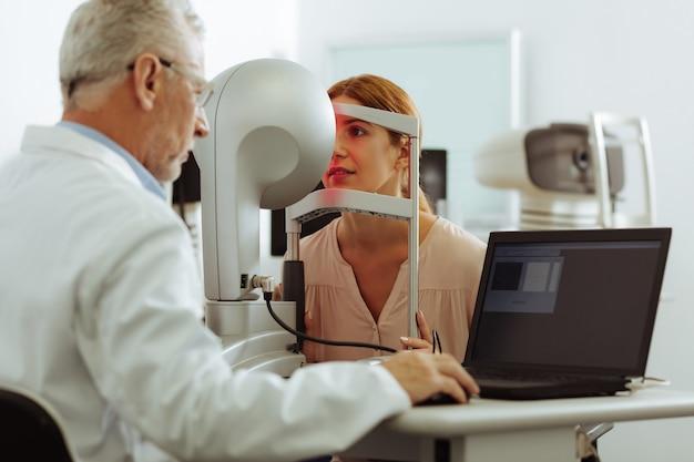Oftalmólogo experimentado. oftalmólogo experimentado examinando a una mujer joven mientras está sentado cerca de la computadora portátil