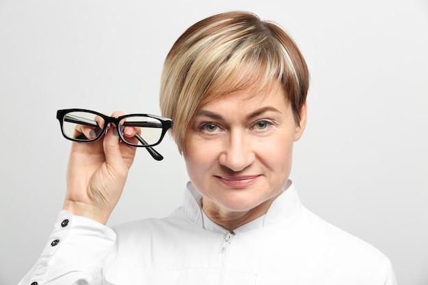 Oftalmólogo mujer madura con gafas sobre fondo blanco.