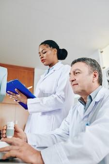 Oftalmólogo que usa la máquina de prueba ocular con refractómetro cuando la enfermera llena la tarjeta médica del paciente