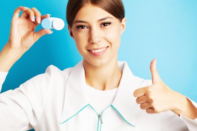 El oftalmólogo sostiene un recipiente con lentes de contacto cerca de los ojos.