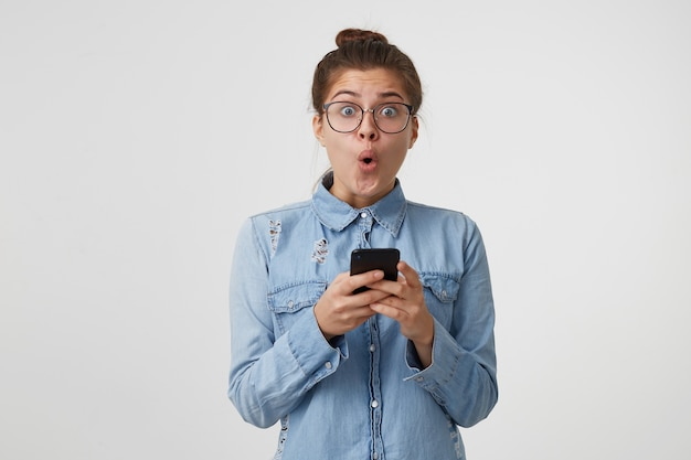Oh dios mío, la mujer sostiene un teléfono inteligente en sus manos, mira a la cámara con los ojos bien abiertos y la boca redondeada con asombro
