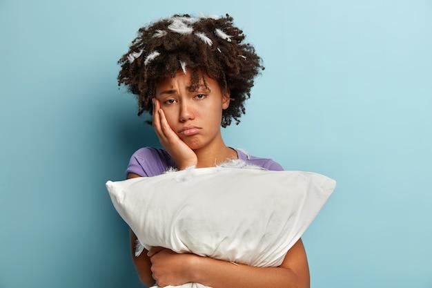 Oh no, quédate a dormir. mujer negra disgustada con exceso de trabajo toca la mejilla, mira con expresión sombría, sostiene la almohada blanca de cerca, tiene expresión infeliz después de un mal descanso, posa sobre una pared azul