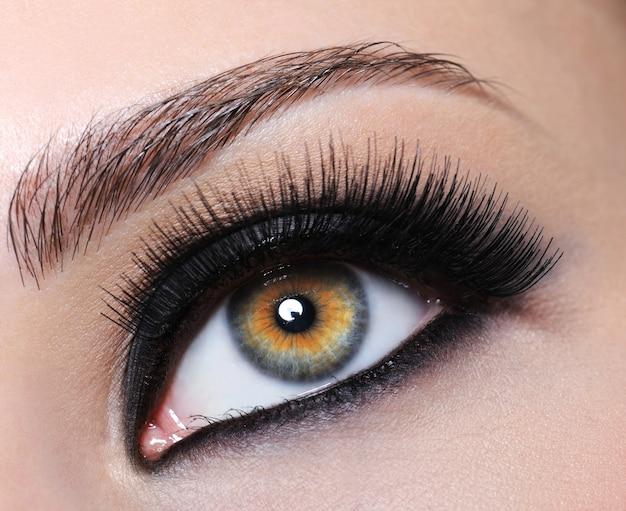 Ojo femenino con maquillaje negro brillante y pestañas largas
