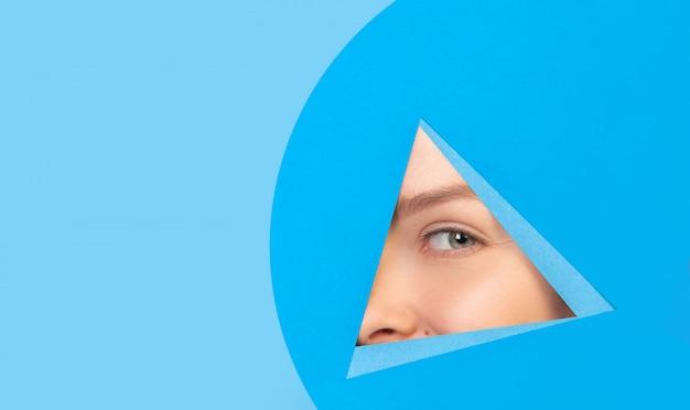 Ojo femenino mirando, mirando a través del triángulo en fondo azul