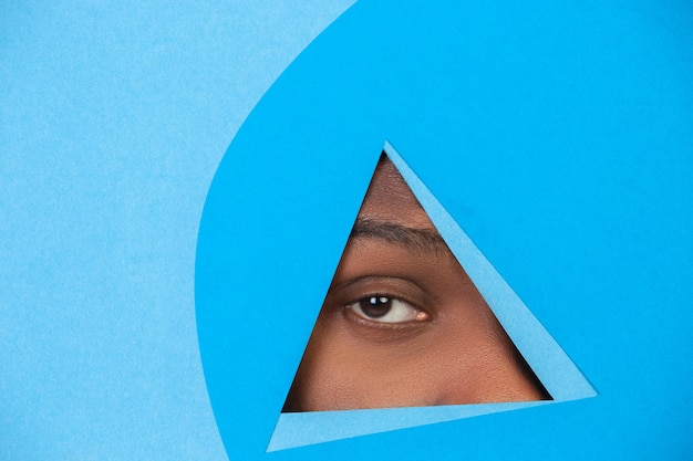 Ojo masculino mirando, mirando a través del triángulo en fondo azul.