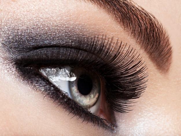 Ojo de mujer con maquillaje de ojos negros. imagen de estilo macro. pestañas largas