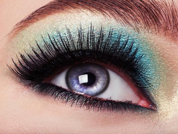 Ojo de mujer con maquillaje de ojos verdes