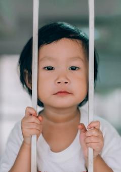 Ojo de tristeza infantil detrás de la puerta de acero, niña asiática