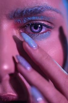 Ojos azules brillantes de un modelo de chica elegante con las manos cerca de la cara en el marco.