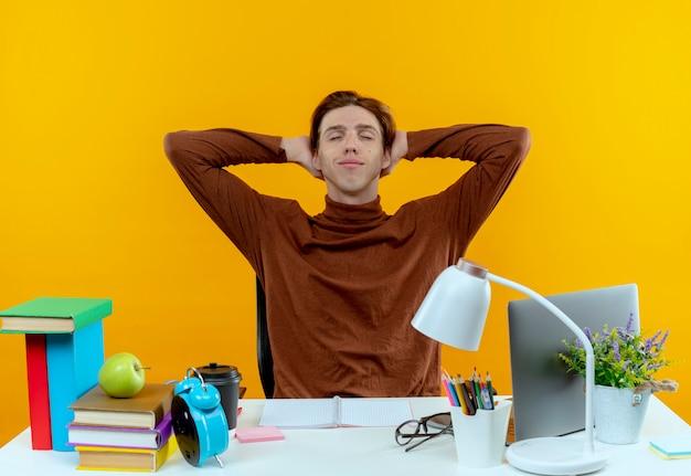 Con los ojos cerrados complacido joven estudiante muchacho sentado en el escritorio con herramientas escolares manteniendo la mano detrás de la cabeza en amarillo