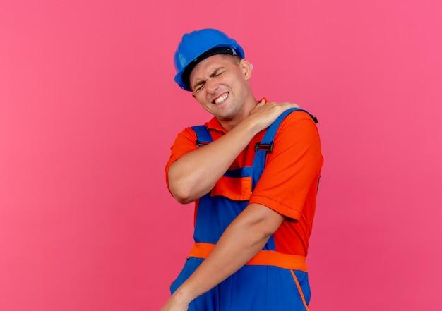Con los ojos cerrados, el constructor masculino joven enfermo vistiendo uniforme y casco de seguridad poniendo la mano sobre el hombro dolorido en rosa