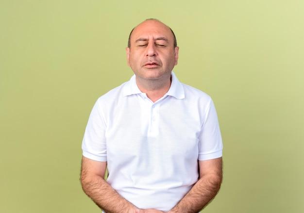 Con los ojos cerrados hombre maduro aislado en la pared verde oliva