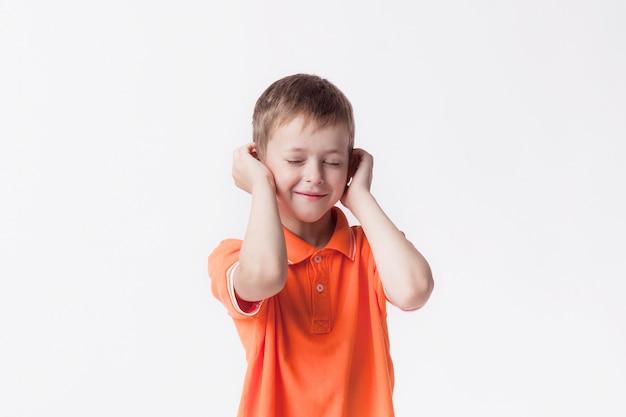 Ojos cerrados niño sonriente cubriendo sus oídos con la mano contra el fondo blanco.