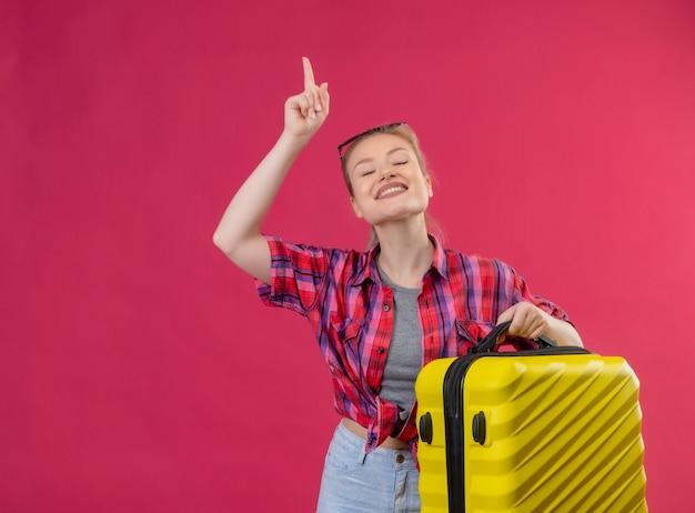 Con los ojos cerrados viajero joven vestida con camisa roja y gafas en la cabeza sosteniendo la maleta apunta hacia arriba sobre fondo rosa aislado