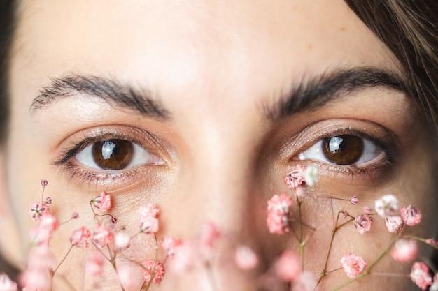 Ojos de mujer bastante marrón y cejas gruesas perfectas con lindas flores secas debajo de los ojos
