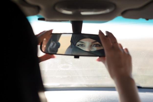 Ojos de mujer musulmana en el espejo retrovisor de un coche.