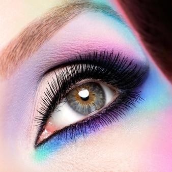 Ojos de mujer de primer plano con maquillaje azul brillante de moda hermosa