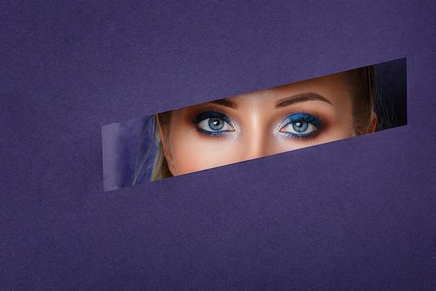 Los ojos de las mujeres hermosas miran en el agujero del papel, maquillaje brillante.