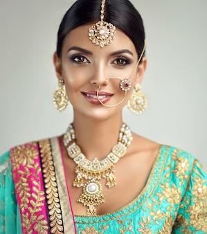 Ojos negros brillantes y sonrisa con dientes en el rostro de una mujer vestida con un conjunto dorado completo de joyas indias