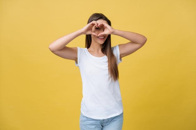Ojos sanos y vision retrato de hermosa mujer feliz sosteniendo las manos en forma de corazón