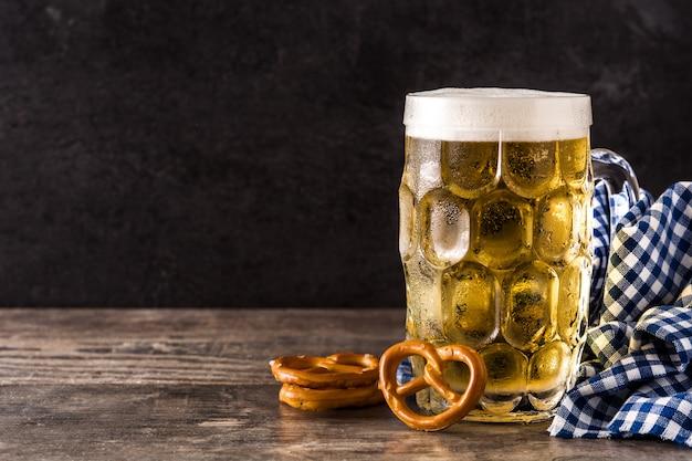 Oktoberfest cerveza y pretzel en mesa de madera.