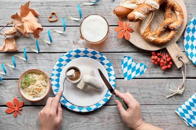 Oktoberfest comida tradicional y cerveza, plano sobre mesa de madera